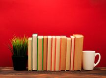 Pile of old books with mug , panorma, good copy space  on red background. Image stock image