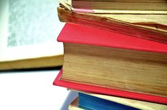 Pile of old books. With an open book in the background Stock Photo