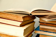 Pile of old books and an open book Stock Photos