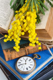 Pile of old books with pocket watch Stock Photos