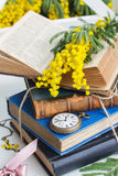 Pile of old books with pocket watch Stock Photo