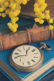 Pile of old books with pocket watch Royalty Free Stock Image