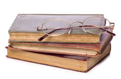 Pile of old books and reading glasses cutout Stock Image