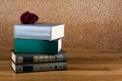 Pile of old books with rose on the b Stock Photo