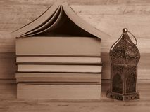 A pile of old home shaped books and a silver Ramadan (Ramazan) lantern. Sepia colour. A pile of old home shaped books and a silver lantern. Sepia royalty free stock images
