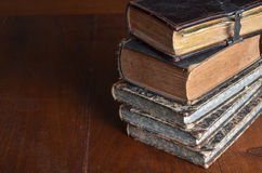 Pile of old books stacked on a wood table
