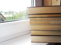 A pile of old books on the white windowsill. Old thick books on white surface royalty free stock photo