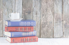 Pile of old books on a wooden retro background and a white worktop stock photo