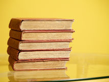 Pile of old books. On yellow background stock photos