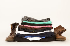 Pile Of Old Clothes And A Pair Of Boots Royalty Free Stock Photos