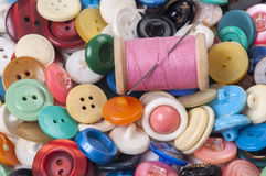 Pile of old colored buttons with thread and needle Stock Photo