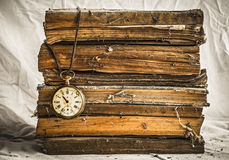 Pile of old dusty books with broken pocket watch on white cloth Stock Photos
