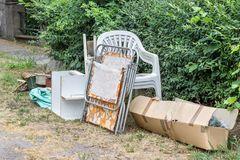 Old furniture and household goods. Pile of old furniture and household items on the roadside stock photo