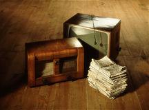Pile of old newspapers, radio and television on wooden floor. Pile of old newspapers, radio and television on brown wooden floor Stock Image