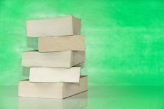 Pile of old books against green background. Pile of old paper books on a table against green background royalty free stock image