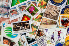 Pile of old random used postage printed stamps from various countries and different time Royalty Free Stock Images