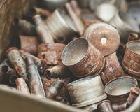 Pile of old rusty shell casings from assault rifles and mounted grenade launchers in metal box Stock Image
