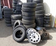 Pile of old tires and wheel rims near the workshop Royalty Free Stock Photos