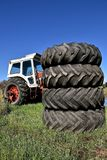 Pile of old tractor tires. A pile of huge stacked tractor tires partially hides a tractor with a cab Stock Images