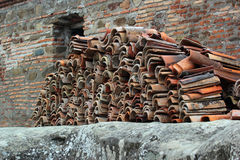 Pile of old used roof tiles. Set against the brick building Stock Photo
