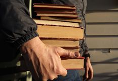Man Holding a Stack of Reading Books in Hand stock photography