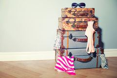 A pile of old vintage travel bags in the room jammed with garmen Stock Photography