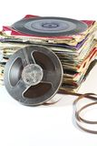 Pile of old vinyl records with a reel to reel tape. Stack of old 7 inch 45s with a retro reel to reel tape Royalty Free Stock Photography