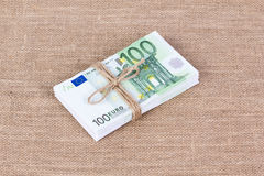 Pile of one hundred euro banknotes tied with rope. On sackcloth background Stock Photo