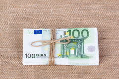 Pile of one hundred euro banknotes tied with rope. On sackcloth background Stock Image