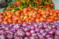 Pile of onions next to a pile of tomatoes and peppers Stock Photos