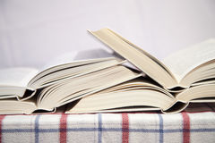 Pile of the opened books. On a table stock photo
