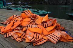 Pile of orange life jackets on a floating dock in ha long bay Royalty Free Stock Photo