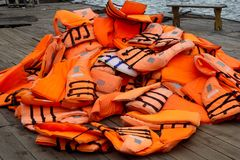 Pile of orange life jackets on a floating dock in ha long bay Stock Image