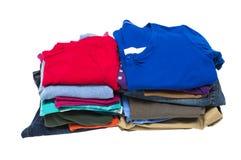 Pile ordinate di vestiti isolati su bianco Immagine Stock