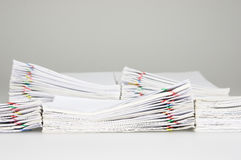 Pile overload document have blur pile paperwork as background. Pile overload document of receipt and report with colorful paperclip have blur pile paperwork as Stock Images