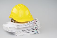 Pile overload document have yellow engineer hat on top. Pile overload document of report and receipt with colorful paperclip have yellow engineer hat on top with royalty free stock image