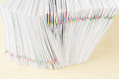 Pile of overload document place in vertical on wooden table. Pile of overload document and reports place in vertical with colorful paper clip on wooden table Royalty Free Stock Photos