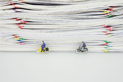 Pile overload paper and miniature people. Pile overload paper with colorful paperclip and miniature people are bicycling on white background Stock Photography