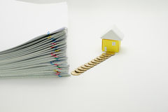 Pile overload paperwork with colorful paperclip. And pile of gold coins with house on white background stock photography
