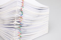 Pile overload paperwork with colorful paperclip on white background Stock Photos