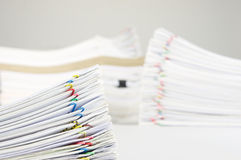 Pile overload paperwork have blur pile document as background. Pile overload paperwork of receipt and report with colorful paperclip have blur pile document as Royalty Free Stock Image