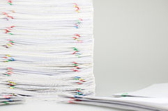 Pile overload paperwork on left have blur pile document around. Pile overload paperwork of receipt and report with colorful paperclip on left have blur pile Royalty Free Stock Image