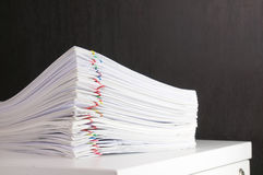 Pile overload paperwork on white cabinet with black wall. Pile overload paperwork of receipt and report with colorful paperclip on white cabinet with black wall Royalty Free Stock Image