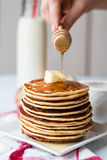 Pile of Pancake with butter, honey sauce add,  hands Stock Photo
