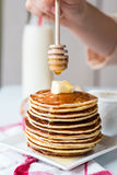 Pile of Pancake with butter, honey sauce add,  hands Stock Photos