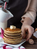 Pile of Pancake with butter, pour honey, hand Stock Photography