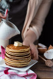 Pile of Pancake with butter, pour honey, hand Royalty Free Stock Image