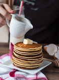 Pile of Pancake with butter, pour honey, hand Royalty Free Stock Photo