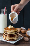 Pile of Pancake with butter, pour honey, hand Stock Photos