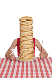 Pile of Pancakes. Little girl with a giant plate of pancakes, a knife and fork on a table cloth stock photo